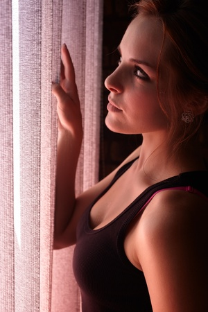 blinders: Beautiful young adult caucasian woman wearing a black top looking at the sunset through the blinders at her window  Stock Photo