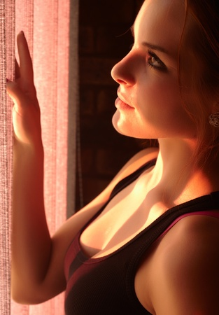 blinders: Beautiful young adult caucasian woman wearing a black top looking at the sunset through the blinders at her window