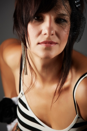 mature brunette: Beautiful and mature adult caucasian woman with red lips, dark hair and brown eyes wearing a  striped black and white top and headpiece Stock Photo