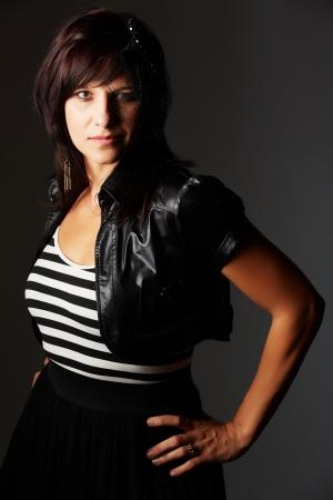 pelo castaño claro: Hermosa y madura mujer cauc?sica adulta joven con labios rojos, pelo oscuro y ojos marrones con una chaqueta de cuero negro, top blanco y negro a rayas y un sombrero de encaje