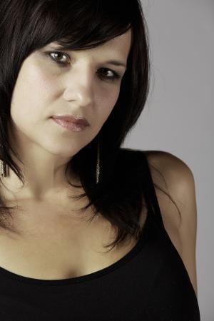 ojos marrones: Hermosa y madura mujer cauc?sica adulta joven con labios rojos, pelo oscuro y ojos marrones llevaba un top negro con los hombros abiertos contra un fondo gris Foto de archivo