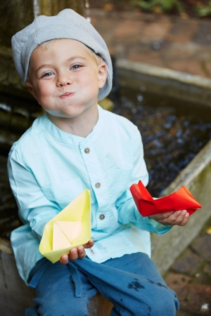 Little four year old boy in a blue outfit playing with paper boats in a small outdoor water fountain photo