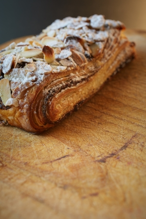 Fresh chocolate and Almond rollover croissant pastry, sprinkled with icing sugar on a brown wooden serving board with copy space  - Shallow Depth of Field (DOF) Stock Photo - 19372965