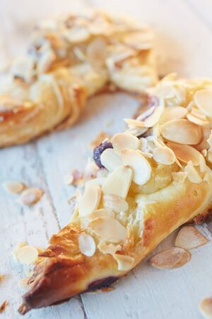 Fresh berry and almond pinwheel pastry, sprinkled with icing sugar on a brown wooden serving board with copy space - Shallow Depth of Field (DOF) Stock Photo - 19372666