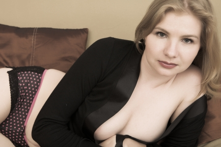 Portrait of a beautiful adult blonde Russian woman with blue eyes wearing a black negligee photo