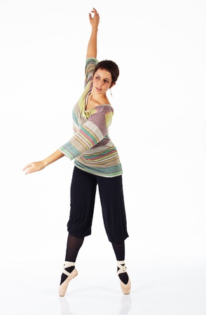 en pointe: Modern female ballet dancer with black pants and a colorful striped jersey en pointe on a white background in various ballet positions.