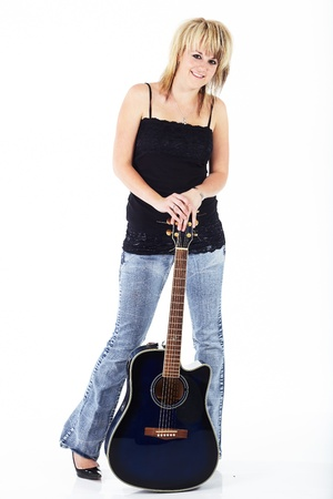 woman guitar: Beautiful young blonde caucasian woman standing with a blue acoustic guitar against a white background Stock Photo