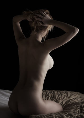 naked woman back: Young beautiful adult caucasian woman with honey blonde hair and full breasts holding her hair up and seen from behind - high contrast images with deep shadows