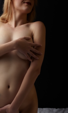 naked woman back: Young pretty adult caucasian woman with honey blonde hair and full breasts sitting up on a bed covering herself with her hands - high contrast images with deep shadows