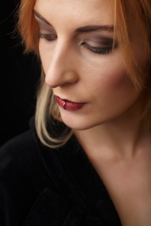 honey blonde: Close up portrait of the pierced red lips of a beautiful young adult caucasian woman in a black gown