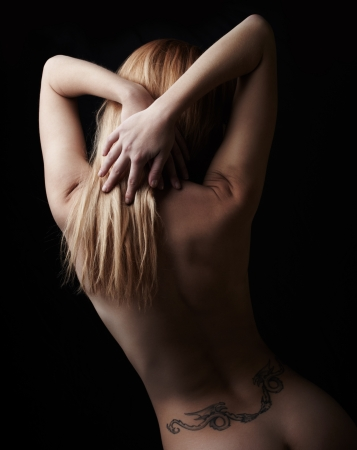 naked woman back: Naked young adult caucasian woman holding her blonde hair up  Shot from behind