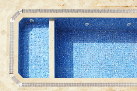 Empty blue tiled swimming pool in a state of disrepair Stock Photo