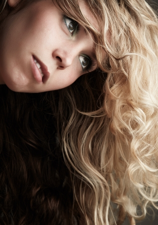 honey blonde: Beautiful young blonde caucasian woman with long curly honey blonde hair in a little black dress on a neutral background