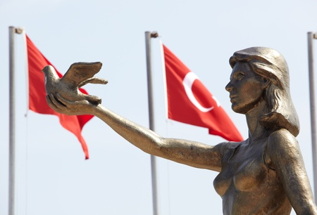 signifies: Monument of Ataturk and Youth, Kusadasi, Turkey with Turkish flags in the background. The monument signifies peace and hope