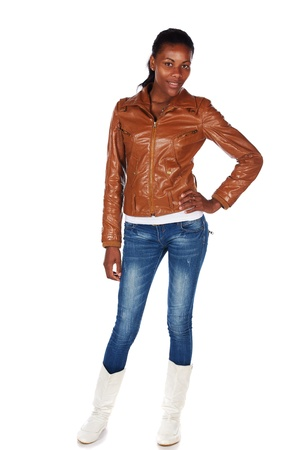 Beautiful black african young adult woman casually dressed in a brown leather jacket and Blue jeans with white boots Stock Photo - 20335107