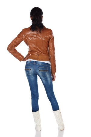 Beautiful black african young adult woman casually dressed in a brown leather jacket and Blue jeans with white boots Stock Photo - 20335235