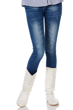 Legs and boots of a stylish and thin black african young adult woman casually dressed in blue jeans and white boots and isolated on a white background Stock Photo - 20334564