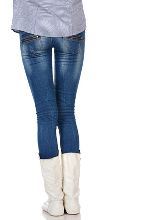 ass jeans: Legs and boots of a stylish and thin black african young adult woman casually dressed in blue jeans and white boots and isolated on a white background Stock Photo