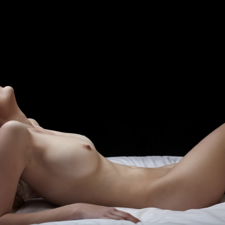 Artistic low key image of a nude adult woman lying on her back against a dark background