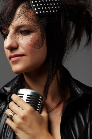 Beautiful and mature adult caucasian woman with red lips, dark hair and brown eyes wearing a black leather jacket and holding a microphone Stock Photo - 20335242