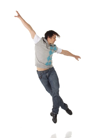 Tap dancer in blue jeans and tap shoes doing steps on a white background and floor