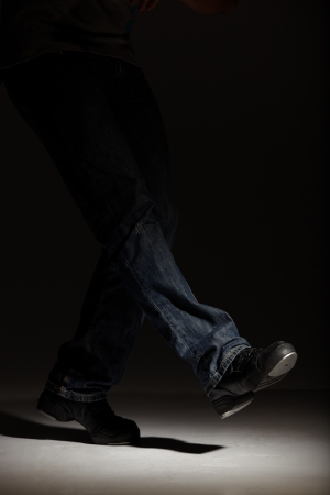 tap dance: Tap dancer in blue jeans and tap shoes doing steps in a spotlight