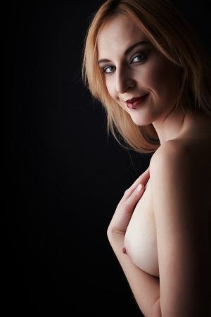 artistic nude: Sideways view of a young beautiful adult caucasian woman with honey blonde hair with her hand on her breasts against a dark background - high contrast images with deep shadows, Copy Space