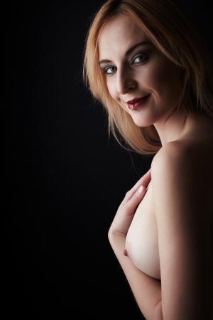 desnudo artistico: Ver las copas de un adulto joven hermosa mujer de raza cauc�sica con miel pelo rubio con la mano en su pecho contra un fondo oscuro - im�genes de alto contraste con las sombras profundas, Espacio en blanco