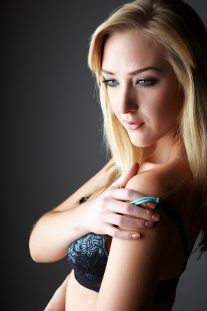 nude blonde girl: Beautiful young adult caucasian woman with blue eyes and shoulder length blonde hair wearing a sexy blue and black bra  Against a neutral background