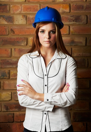 black pants: Beautiful young adult caucasian woman wearing a blue safety hat, black pants and a white shirt in front of a brown brick wall with crossed arms