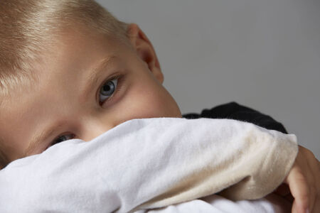 light complexion: 5 year old caucasian boy with short blonde hair, blue eyes and a light, healthy complexion wearing a long sleeve t-shirt. Shot in studio on a grey background. Stock Photo