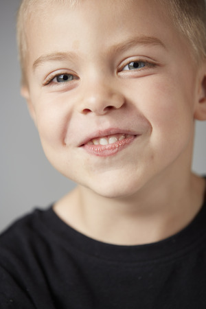 light complexion: 5 year old caucasian boy with short blonde hair, blue eyes and a light, healthy complexion wearing a long sleeve t-shirt. Shot in studio on a grey background - very shallow depth of field