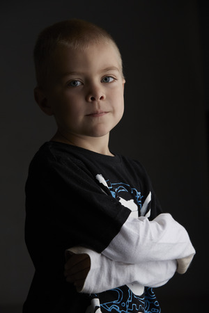 light complexion: 5 year old caucasian boy with short blonde hair, blue eyes and a light, healthy complexion wearing a long sleeve t-shirt. Shot in studio on a dark grey background.