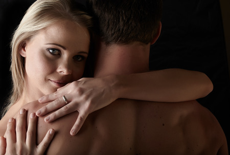 Young and fit caucasian adult couple in an embrace. Semi-nude and topless against a dark background . photo