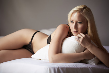 Beautiful and very sexy young adult caucasian woman in Black lingerie with blonde hair and blue eyes, in a bedroom setting with typical boudoir poses photo