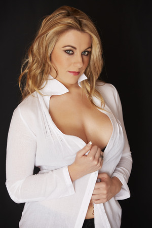 big breast woman: Sexy and beautiful full figured young adult caucasian woman in black lingerie and an open white shirt against a black background Stock Photo