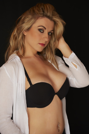 breasts pretty: Sexy and beautiful full figured young adult caucasian woman in black lingerie and an open white shirt against a black background Stock Photo