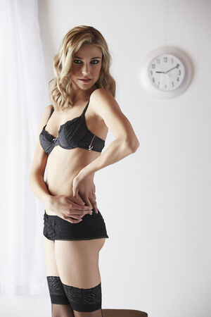 sheer lingerie: Sexy and beautiful young adult caucasian blonde woman in black lingerie and stockings in a light white bedroom