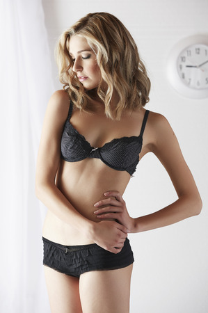 sheer lingerie: Sexy and beautiful young adult caucasian blonde woman in black lingerie in a light white bedroom Stock Photo