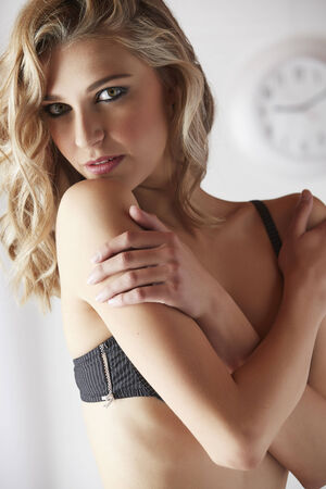foreplay: Sexy and beautiful young adult caucasian blonde woman in black lingerie in a light white bedroom Stock Photo