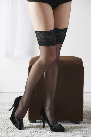 stockings heels: The legs of a sexy and beautiful young adult caucasian woman in black lingerie and stockings in a light white bedroom
