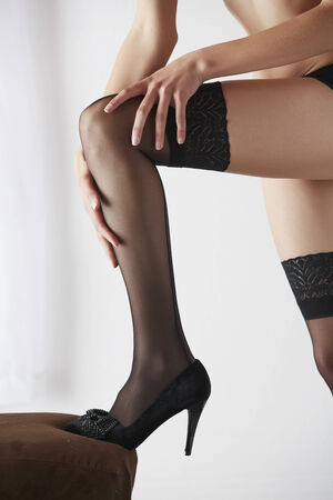 sheer lingerie: Sexy and beautiful young adult caucasian woman in black lingerie and stockings in a light white bedroom