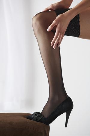 pantimedias: Las piernas de una mujer adulta joven caucásica atractiva y hermosa en ropa interior negro y medias en un dormitorio de la luz blanca