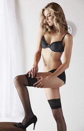 pantimedias: Adulto joven, caucásico, mujer rubia atractiva y hermosa en ropa interior negro y medias en un dormitorio de la luz blanca