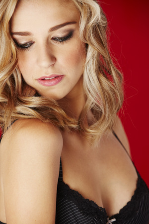 sheer lingerie: Sexy and beautiful young adult caucasian blonde woman in black lingerie against a red background Stock Photo