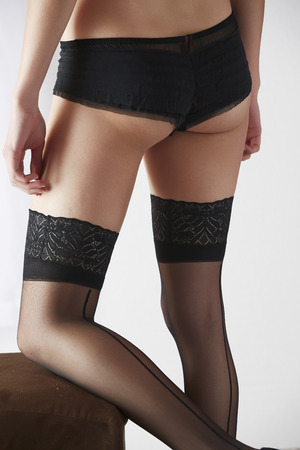 sheer lingerie: The bum of a sexy and beautiful young adult caucasian woman in black lingerie and stockings in a light white bedroom Stock Photo
