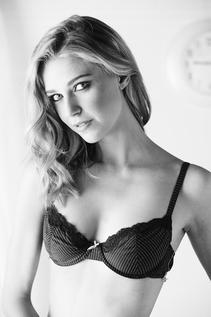 sheer lingerie: Sexy and beautiful young adult caucasian blonde woman in black lingerie in a light white bedroom