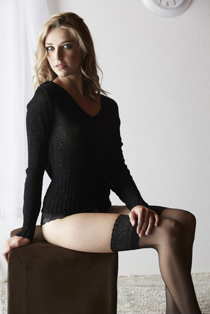 to undress: Sexy and beautiful young adult caucasian woman in black lingerie and a knitted see through hoodie in a light white bedroom