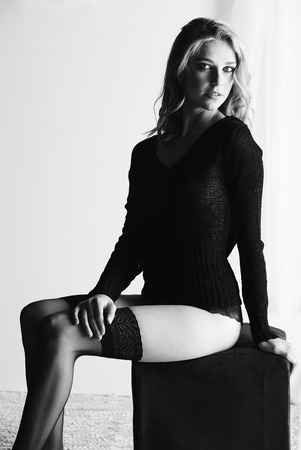sheer lingerie: Sexy and beautiful young adult caucasian woman in black lingerie and a knitted see through hoodie in a light white bedroom