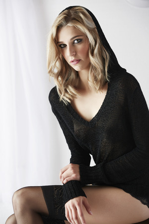 the girl in stockings: Sexy and beautiful young adult caucasian woman in black lingerie and a knitted see through hoodie in a light white bedroom